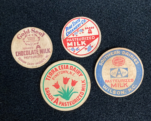 Old style lids for milk jugs from four North Carolina dairies