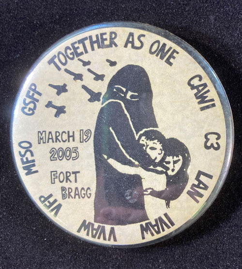 """Pinback with ffemale figure in hijab clutching two children. The words read """"Together as one"""" and """"March 19, 2005"""""""