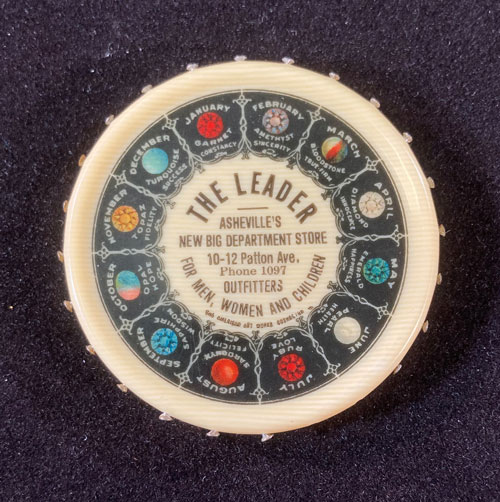 """Circular plastic item with images of birthstones around the edge and the words """"The Leader, Asheville's New Big Department Store"""" and the store's address in the center."""