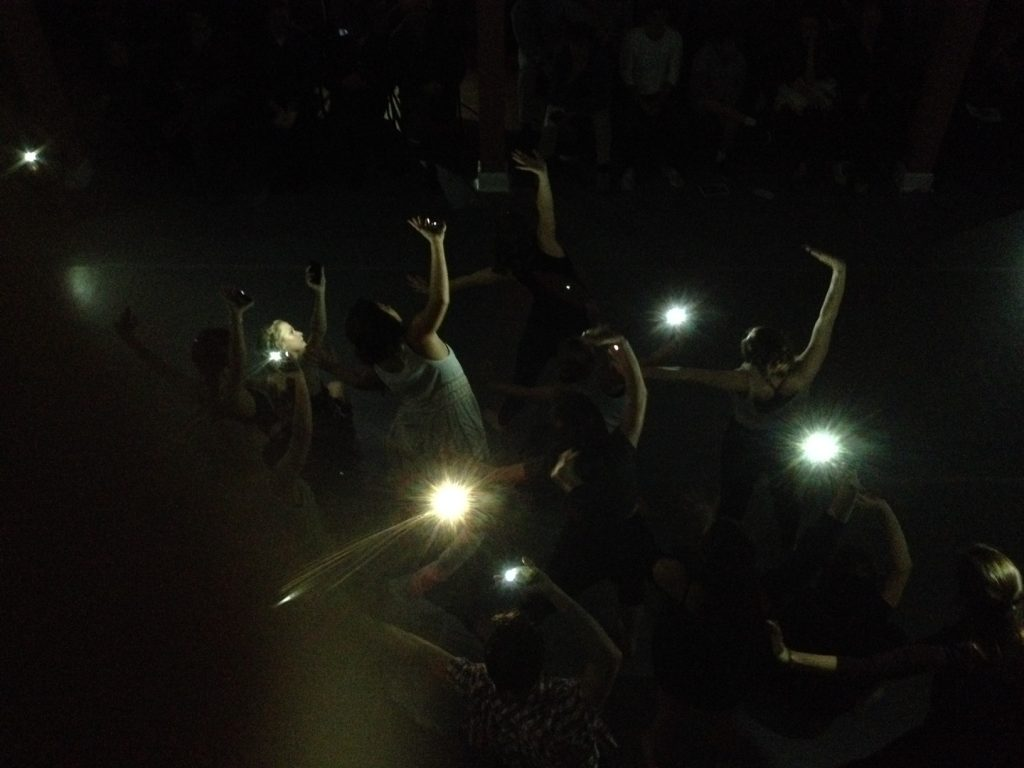 Dancers on the floor with their smartphones.