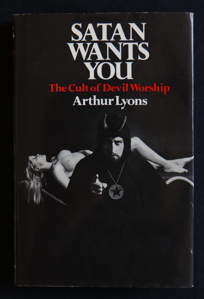 "The cover of Arthur Lyons's Satan Wants You, the title in all caps and white text with a red subtitle in the same font that reads ""The Cult of Devil Worship"". On the cover, a black and white photo of Anton LaVey dressed in Satanic ritual robes and posing as Uncle Sam in front of a nude model lying on an altar."