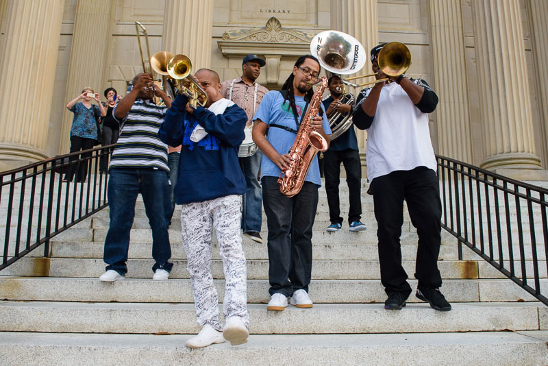 Rebirth Brass Band lead the second line down the steps of Wilson Library. Photo by Mark Perry Photography.