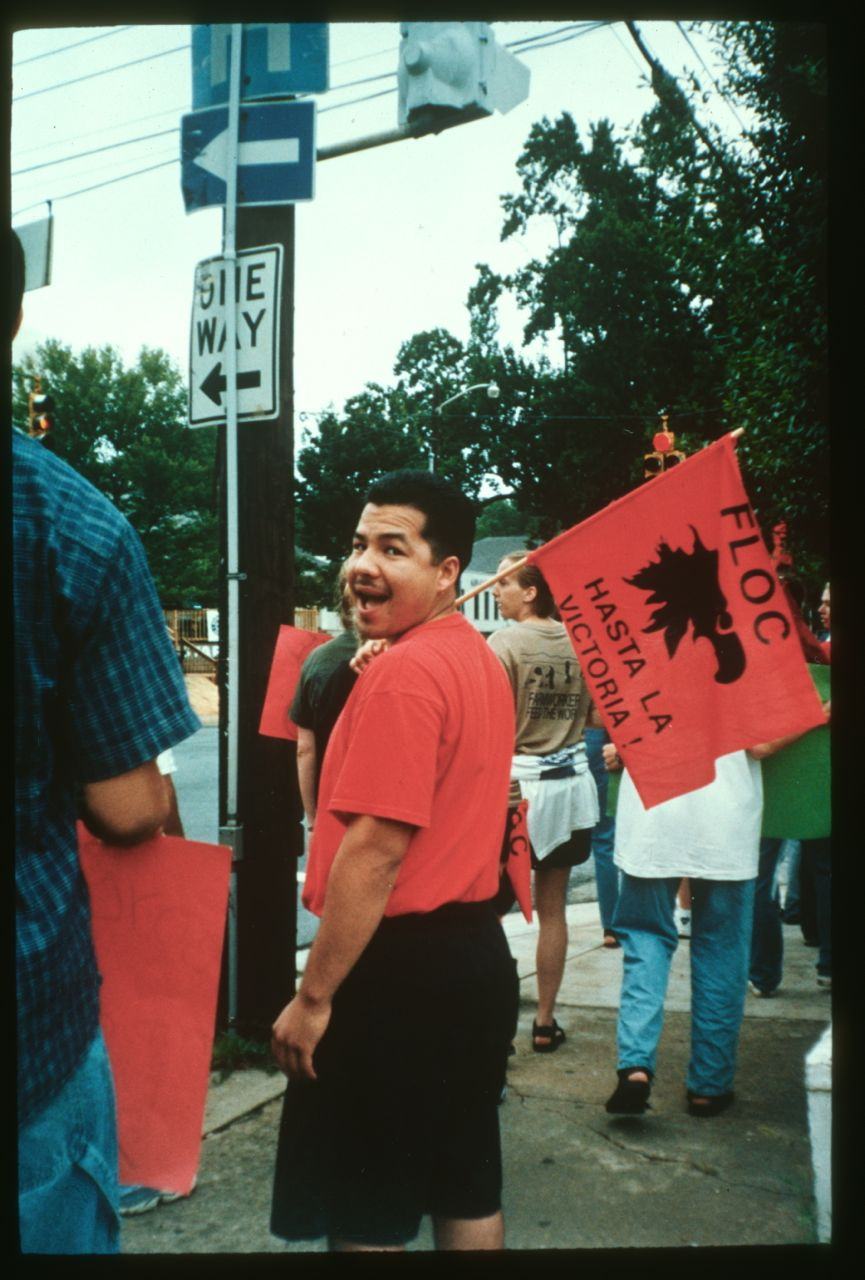 "Ramiro Sarabia, Jr., member of the Farm Labor Organizing Committee, holding ""¡Hasta La Victoria!"" sign at the Mount Olive Pickle Protest, July 1999. Photo by Lori Fernald Khamala and Mendi Drayton. Student Action with Farmworkers Collection (20317), Southern Folklife Collection."