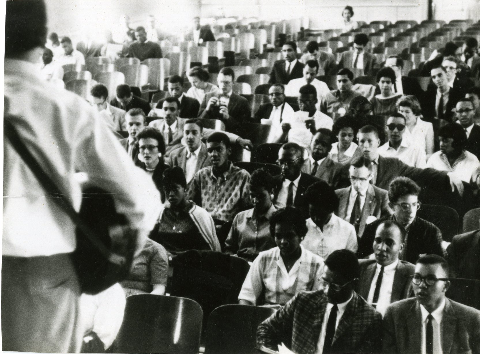 The back of Guy Carawan singing to audience in auditorium at Shaw University, Durham, NC, 1960. Founding meetings of SNCC.