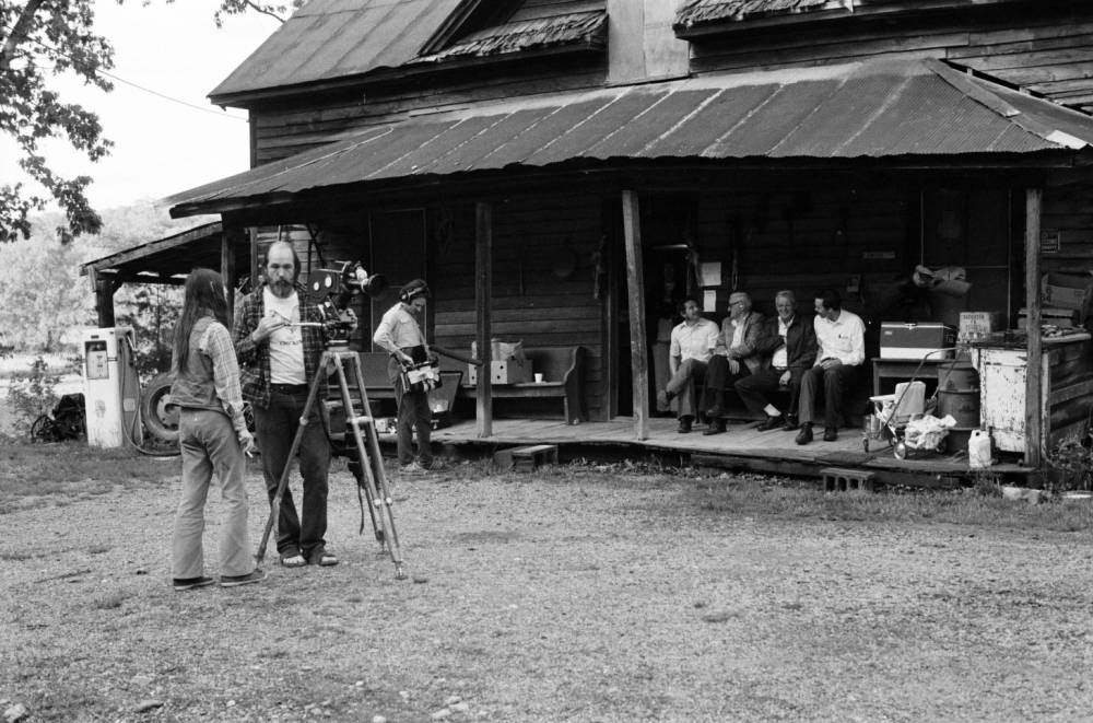 Photograph of filmmakers Les Blank and Cece Conway standing by camera that points towards Tommy Jarrell and others sitting on the porch of his home in Toast, NC.