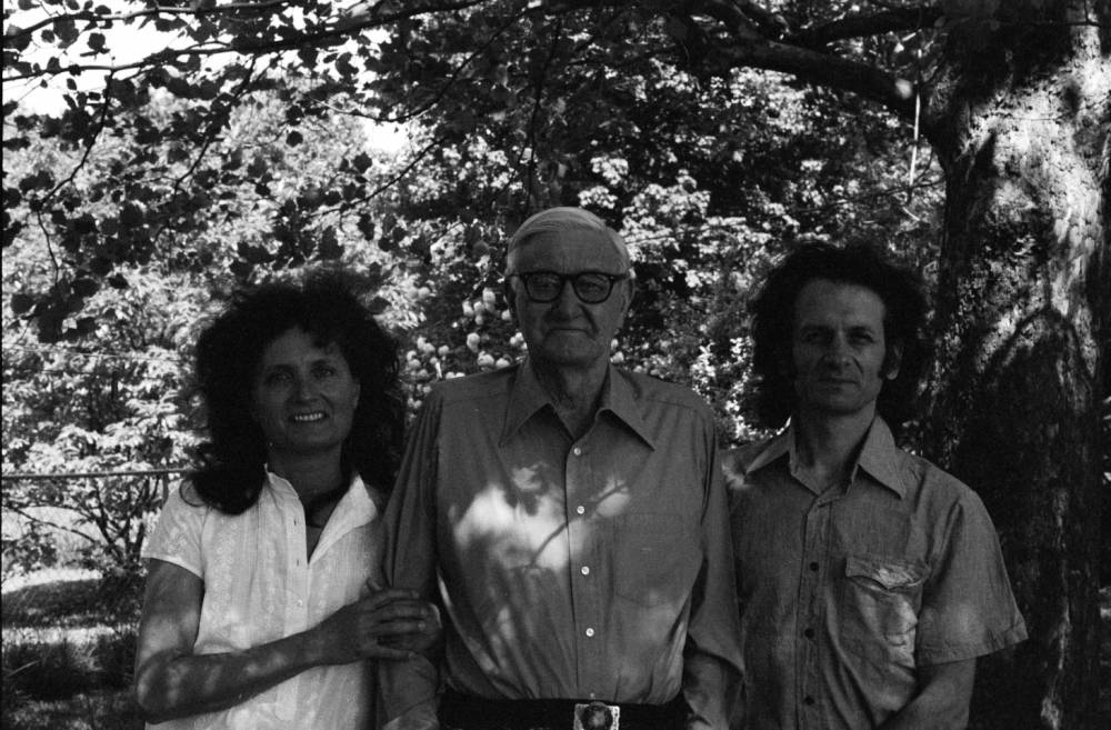Filmmaker Alice Gerrard and sound person, Mike Seeger, posing with Tommy Jarrell in front of a tree.