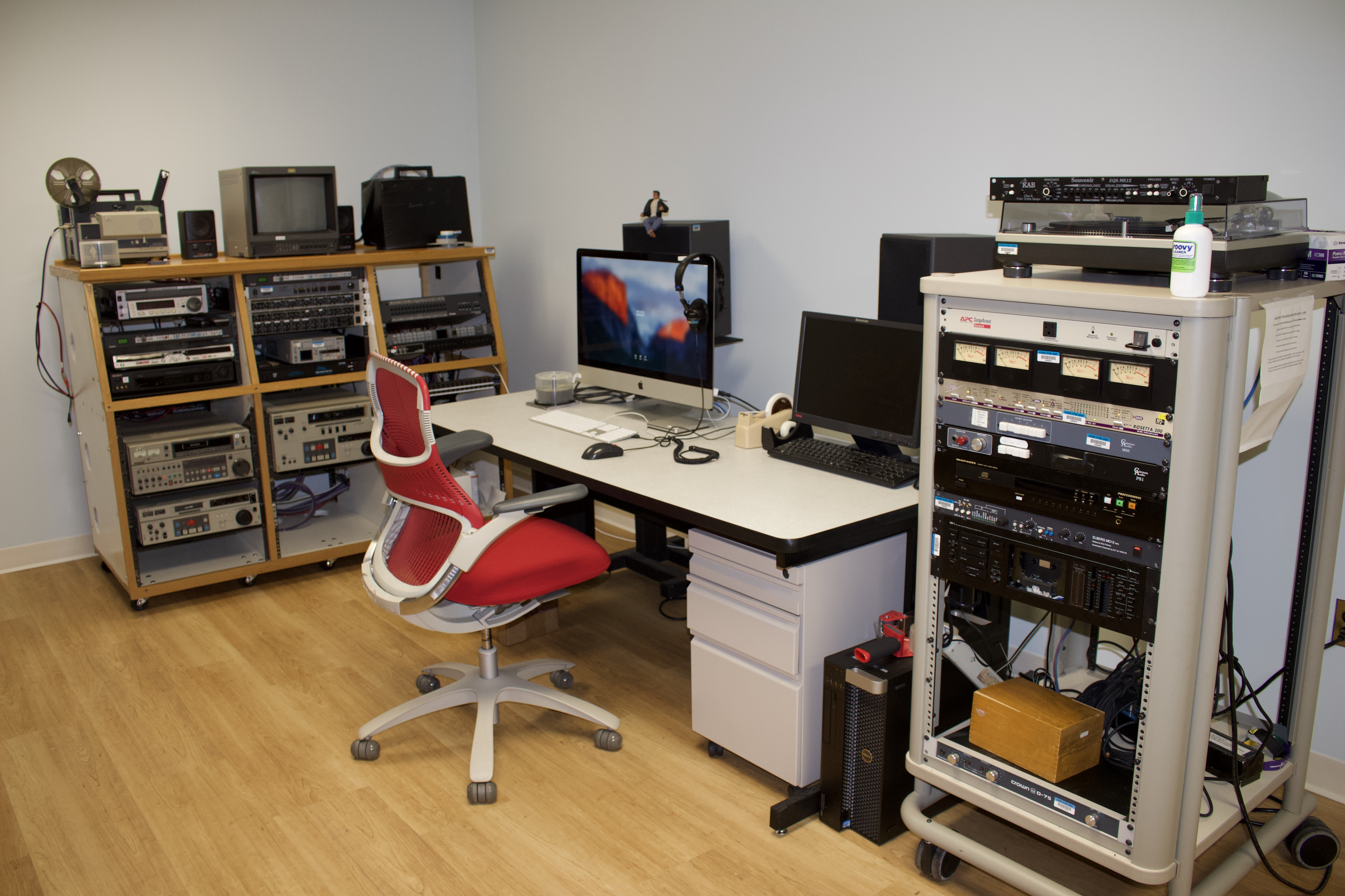 a vertical rack of audio equipment sits next to a table with computers, with a rack of video equipment in the background