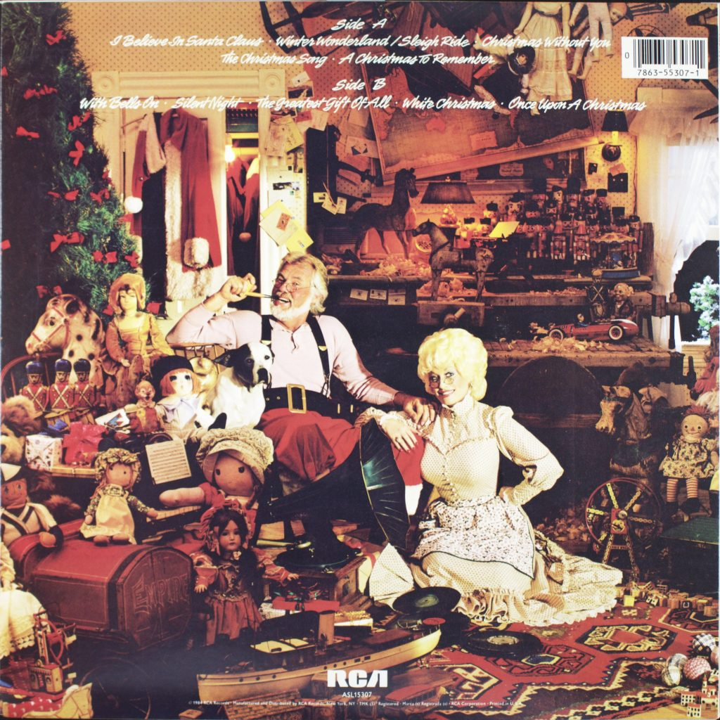 Kenny Rogers and Dolly Parton dressed up sort of like Mr and Mrs. Santa Claus sitting in a room decorated for Christmas holidays