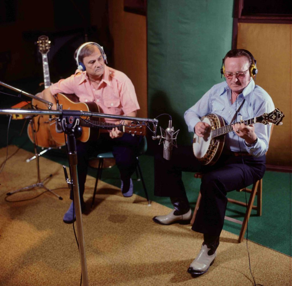 In a recording studio, seated in front of microphones, Arthur Smith, late middle aged, wearing headphones, in a red short sleeve shirt and purple boots holds a guitar, Don Reno, wearing headphones and classes, with blue longsleeve shirt, blue pants, and cowboy boots, playing a banjo