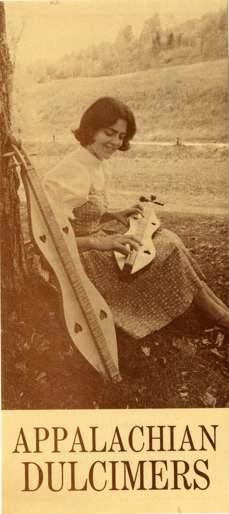 "Sandy Paton holding a dulcimer while sitting by a tree, advertisement for ""Appalachian Dulcimers"""