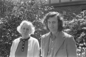 Eudora Welty on left in white sweater, Bill Ferris on right with sport coat. they are standing outside