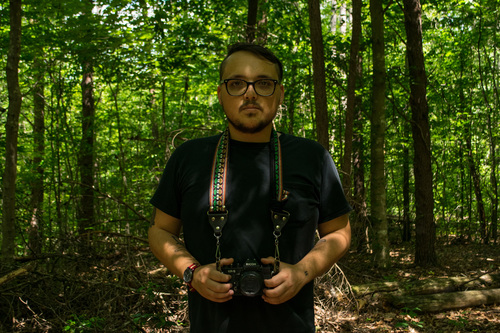 Phillip MacDonald standing in the woods holding a camera