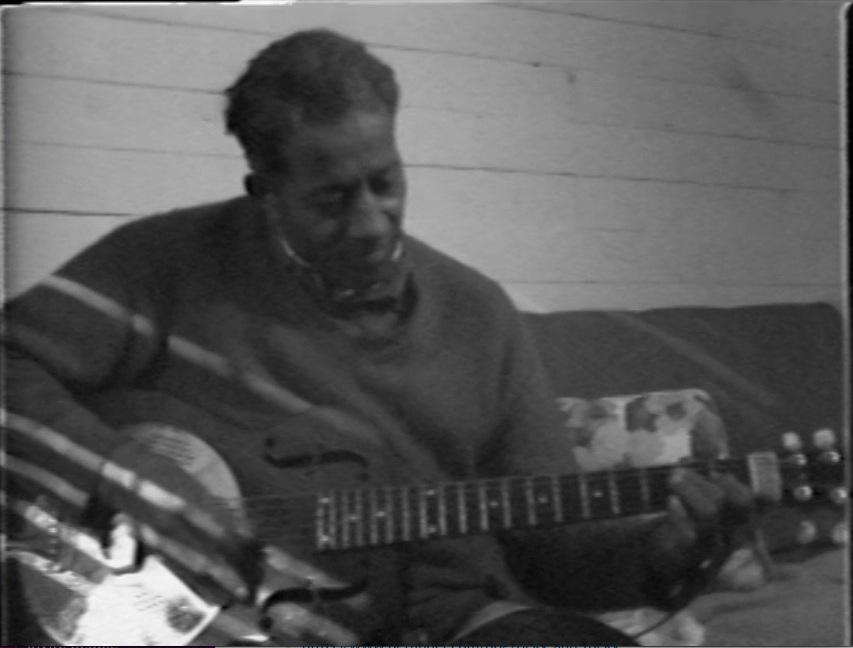 Black and white shot of man sitting on couch, playing a guitar.