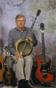 Bobby Patterson seated, holding a banjo with a mandolin and electric bass on either side of him