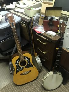 a guitar and two banjos leaning up against a desk in Patterson's studio