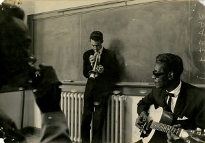 Picture in school room in front of blackboard of three musicians, Joe Chambers on harmonica, Kenny Whitson on cornet, and Lightnin' Hopkins on guitar.