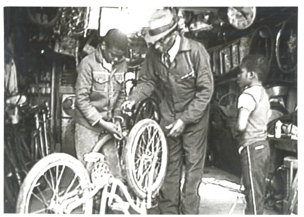 A 1983 photo of an African American man and two young boys working on a bicycle; from journalist, Charles Kuralt's Collection (#04882) in the Southern Historical Collection