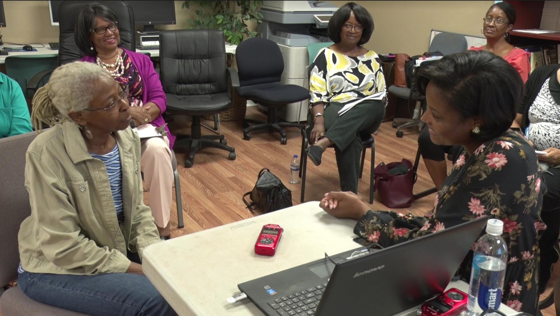 Group of African American women-presenting people sitting in a circle--two of them at the center are conducting an oral history interview. An audio recorder and a laptop computer are sitting on the table between them.