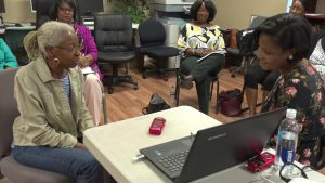 A group of African American women-presenting people sit in a circle with two people at the center participating in an oral history interview. A laptop computer and a digital audio recorder sits between them.