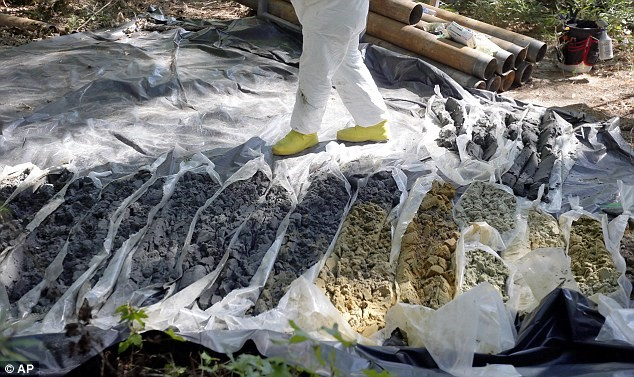 EPA officer stands on plastic sheeting with more than a dozen soil and rock samples to check for contamination.