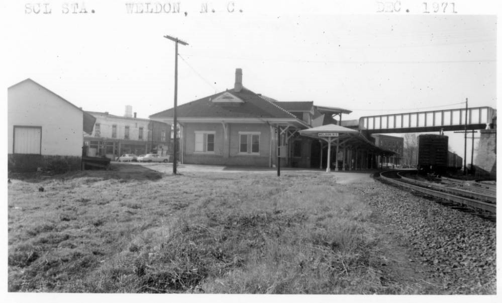black and white photograph of a railroad station. Pictured are the railroad tracks, the station and station platform, and a few buildings of the town in the background