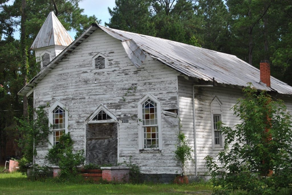 Image of a dilapidated church. The white paint is peeling off of the exterior walls and the door is barred, but the stained-glass windows are still intact, and the reds, yellows, and blue panes are vibrant.