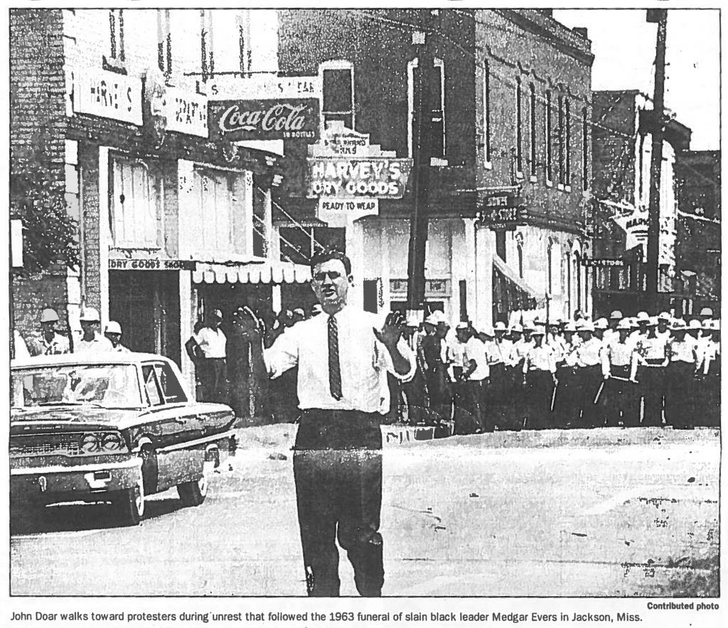 A white man walks toward the camera with a crowd of policemen behind him
