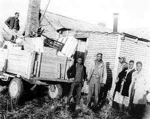 An African American family loading household items into a flatbed truck