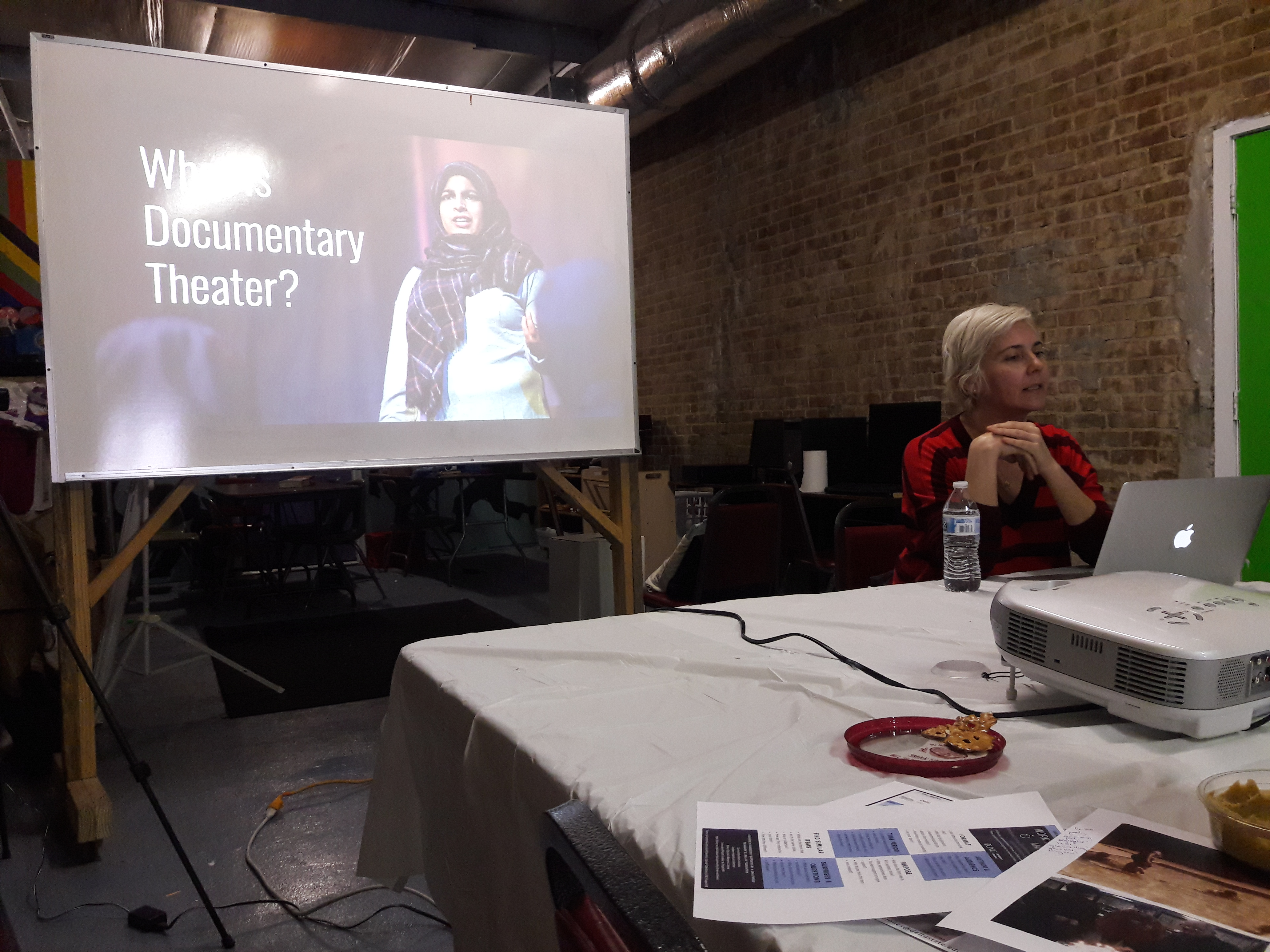 """White woman-presenting person at a table in front of a computer, presenting in front of a screen with a projection. The projected slide features a person in a head scarf and reads, """"What is Documentary Theater?"""""""