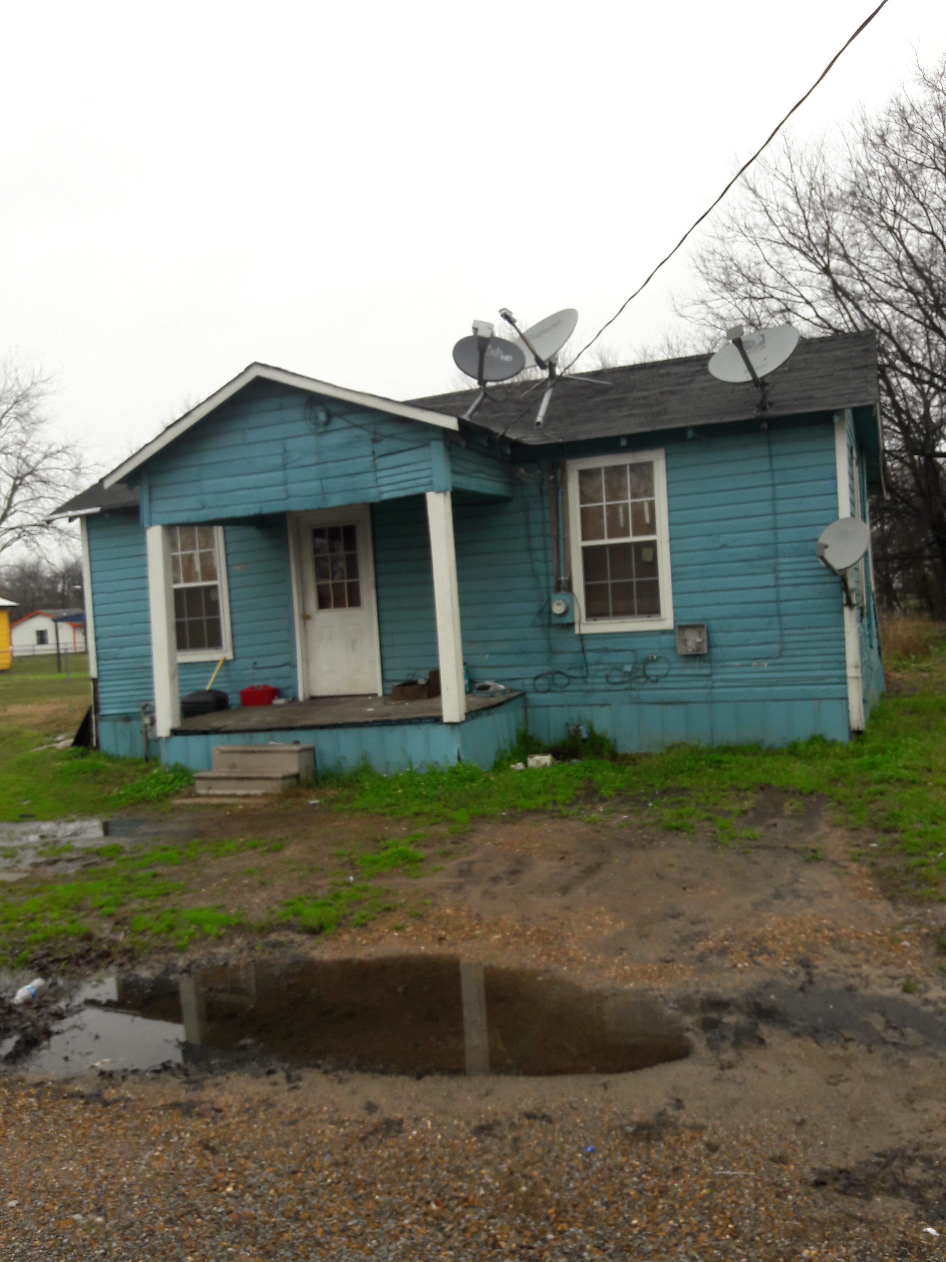 A clapboard-sided blue house with a small porch sitting behind a dirt yard with pooling water.