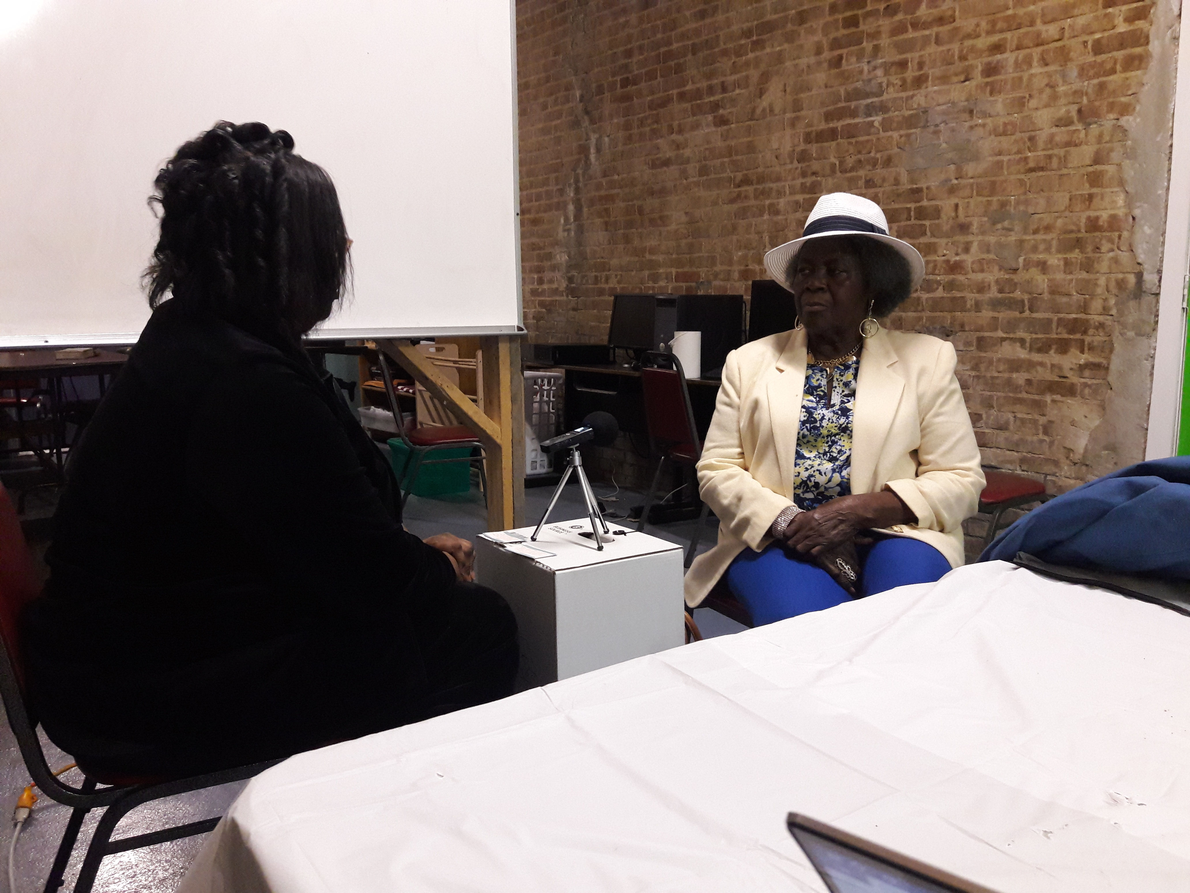 Two African-American women-presenting people seated, talking with an audio recorder on a tripod between them.