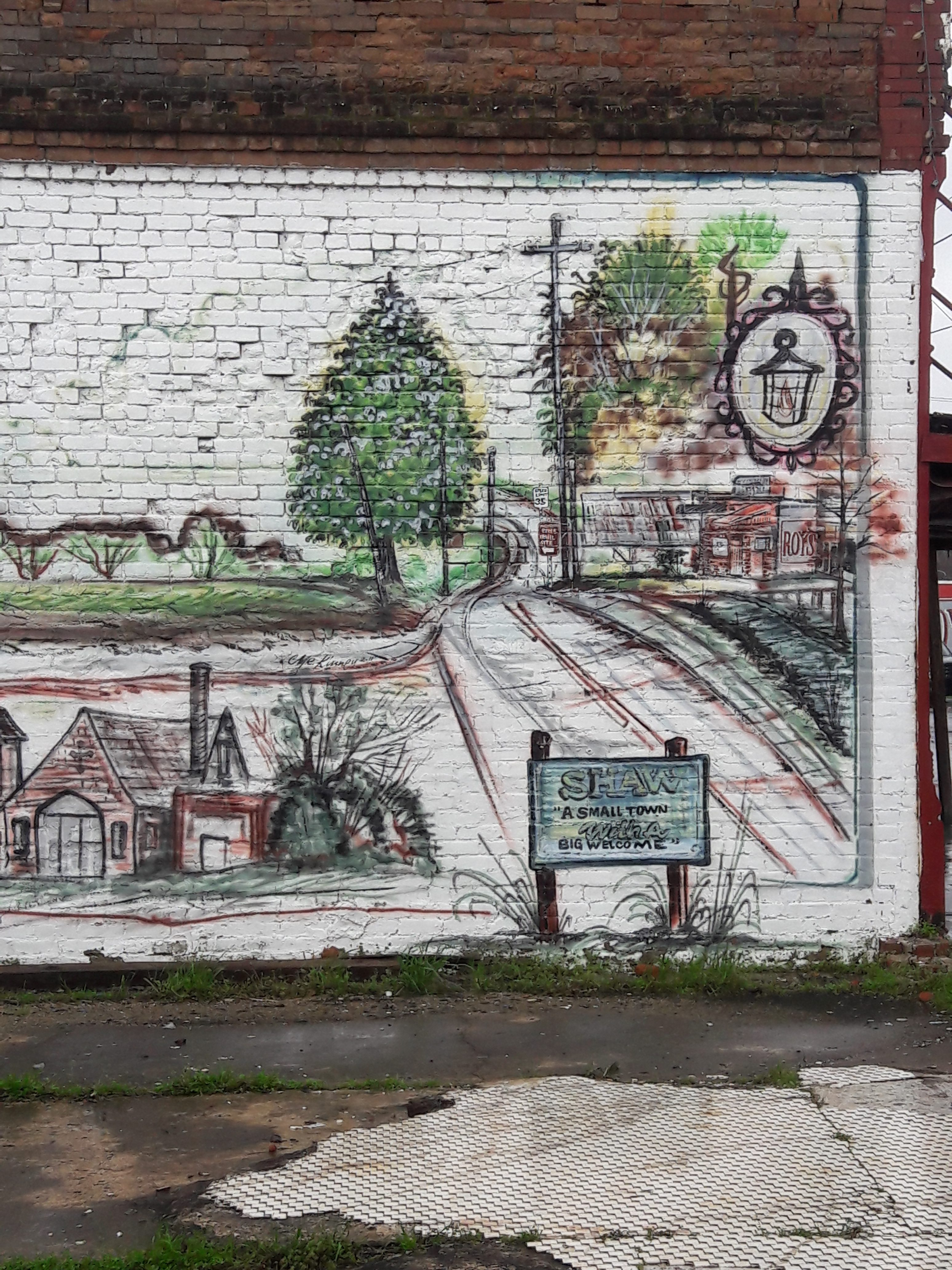 """A mural feautring the town of Shaw, with a lamppost, railroad tracks, businesses, and a church pictured. A sign at the bottom reads: """"Shaw: A Small Town with a Big Welcome."""""""