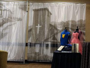 a museum exhibit with a backdrop of a church featuring men's and women's clothing on two mannequins near a table of historical artifacts