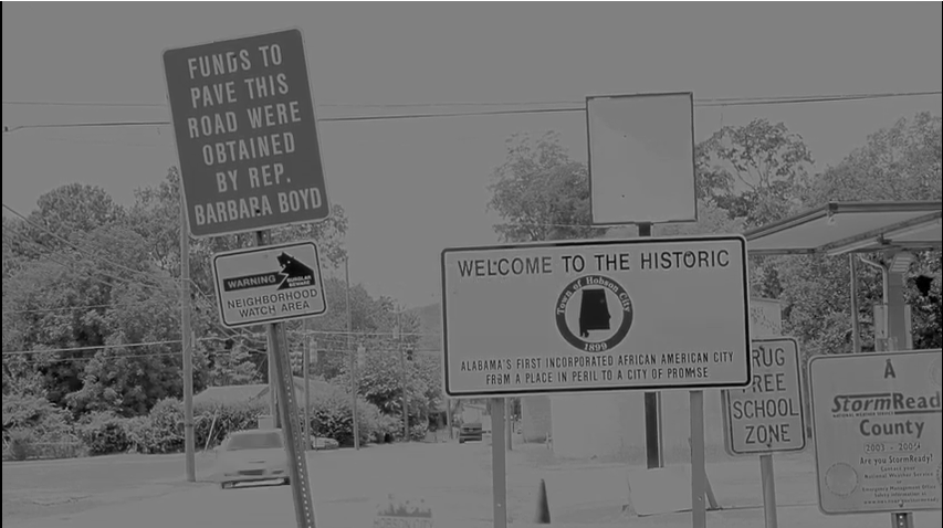 Black and white images of road signs, with one priminent sign reading: Welcome to the Historic Hobson City