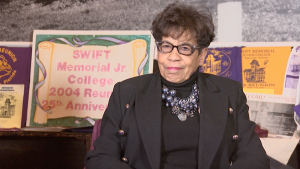 "A Black person seated in from of a sign in the background reading ""Swift Memorial Jr. College Reunion"""