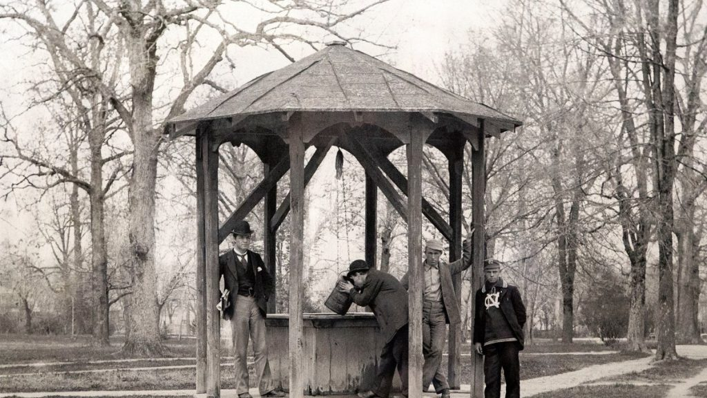 A black and white image of four white male-presenting people in front of the Old Well at UNC