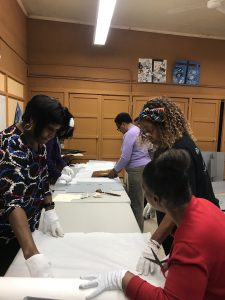 Group of femme-presenting Black people wearing white gloves around a table covered with historical objects, which they are wrapping in white paper