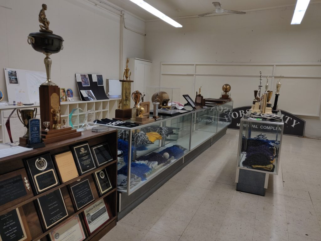 Room filled with museum cases and an array of plaques, trophies and other historical items