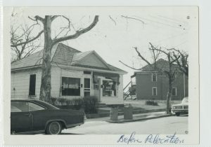 "Black and white photograph of a small white building resembling a house along a tree-lined street with a sidewalk and cars parked along the side. A handwritten note, ""Before Relocation"" is in the lower right hand corner"