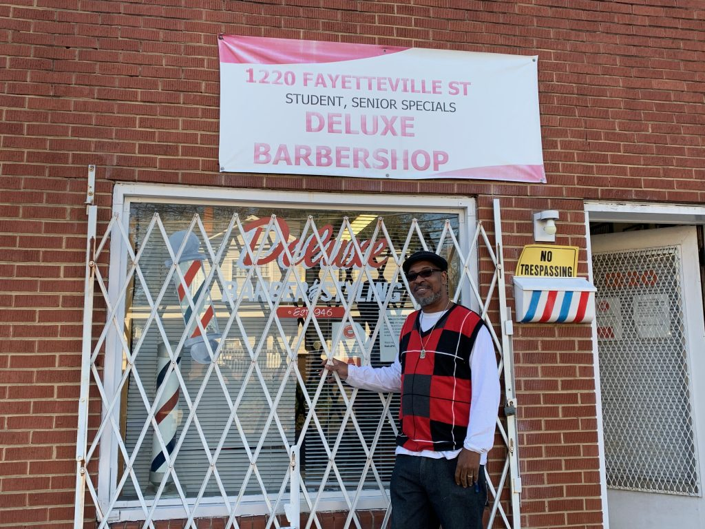 "Black masculine-presenting person wearing sunglasses in front of a building with a sign reading, ""1220 Fayetteville St. Student, Senior Specials, DeLuxe Barbershop."" White bars cover the window and door."