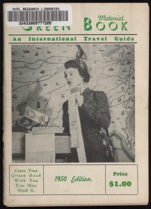 "Cover of the ""Negro Motorist Green Book: An International Travel Guide, 1950 Edition,"" featuring a person standing in front of a map background holding maps and pamphlets"