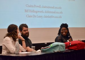 Three people seated behind a table who are part of a panel presentation. Chaitra Powell, who is holding the mic, looks at Biff Hollingsworth and Claire Du Laney. All are smiling. Behind them projected on a large screen are their names and email addresses.