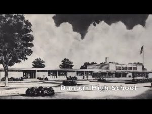 """A black and white image of a school overlaid with the name, """"Dunbar High School"""""""