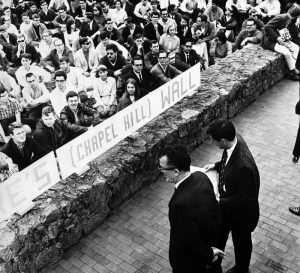 """Two men stand on one side of a low rock wall on the UNC Chapel Hill campus, across from a large crowd on the other side. A partially visible sign on the wall says """"Chapel Hill Wall"""""""