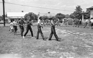 A group of African American men and women march single-file around a yard surrounded by houses.