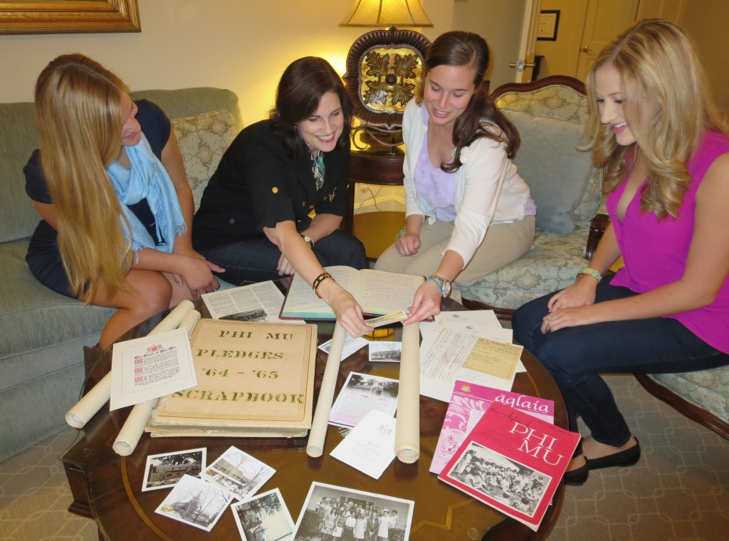 Phi Mu Chapter Association (alumnae) President Debra Pickrel (center left) shows University Archives and Records Management graduate assistant Morgan Jones a construction photo of the sorority's house at 211 Henderson Street as Chapter Historian Lauren Spoenimon (far left) and Chapter President Mary Maher (far right) look on.