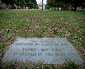 """A plaque on a lawn that reads """"time capsule dedicated by class of 1988/Buried May 1988 to be opened in the year 2013"""""""