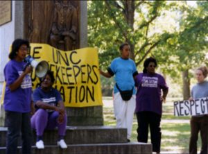 """A color photo of UNC housekeepers holding a sign that reads """"The UNC Housekeepers Association"""" in front of the """"Silent Sam"""" Confederate monument on the UNC campus."""