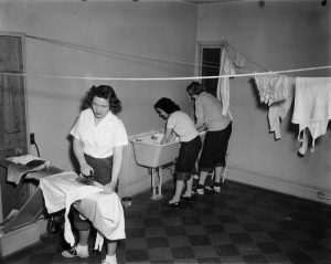 A black and white photo of women students doing laundry in a dormitory in 1948.