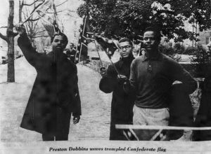 Black students, including Preston Dobbins, waving Confederate flags which they later burned.